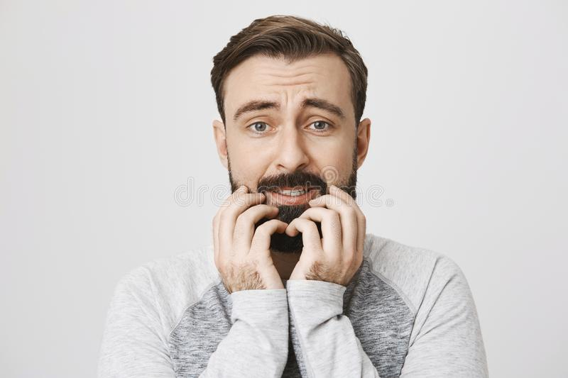 Close-up portrait of european man who expresses fear, holding hands on beard and looking afraid at camera, standing over royalty free stock photos