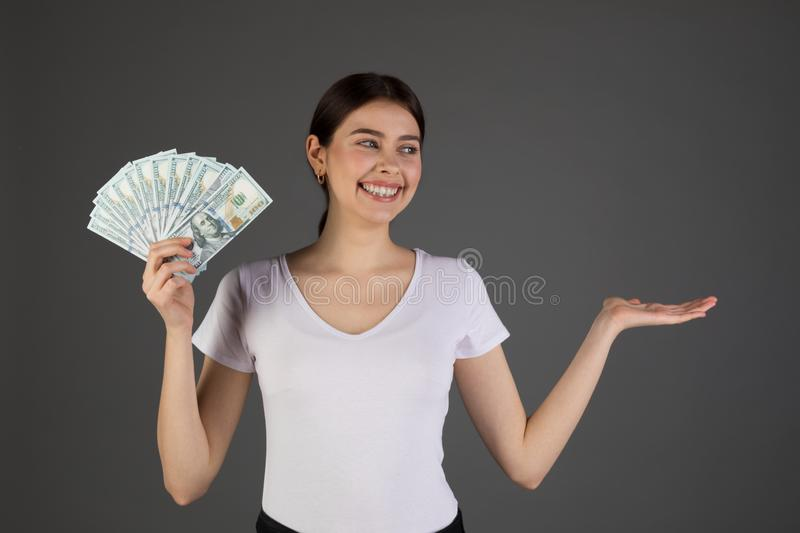 Close up portrait of eurupean woman holding money  on grey background. Girl counting her salary dollar note. Succes wealth financial business cashflow currency royalty free stock images