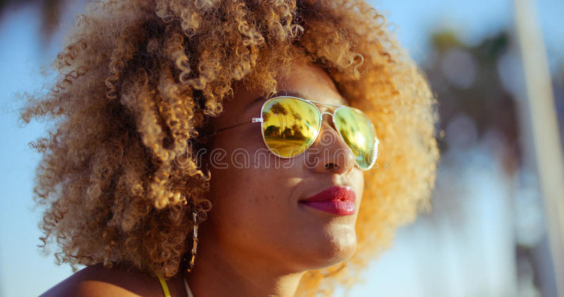 Close Up Portrait of Exotic Girl with Afro Haircut. Wearing Sunglasses with Exotic Trees in Reflection. All on Slow Motion Video stock images