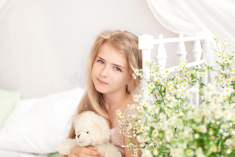 A close-up portrait of the face of a cute little girl hugs a teddy bear, looks at the camera and smiles, sitting at home on the be. D and with a bouquet of wild stock images