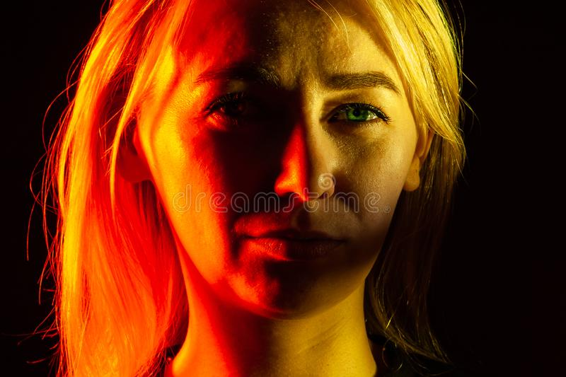 Close up portrait of face an serious girl with bright green eye looking into camera: straight nose, expressive eyes, ears, blonde royalty free stock images