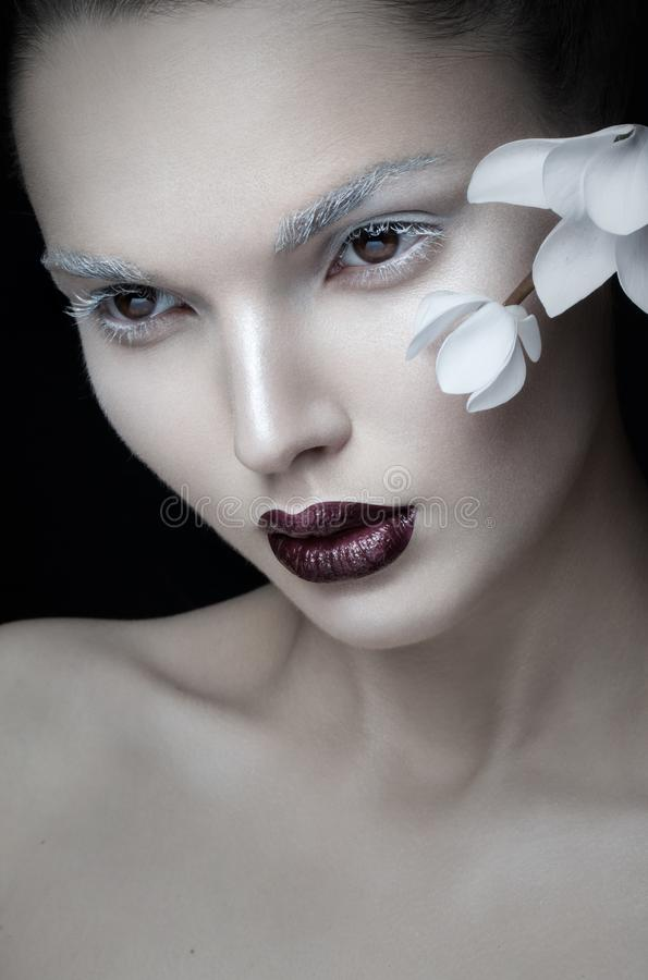 Frontal view of beauty portrait artistic makeup, burgundy lips, face, near white flower, isolated on black background. stock image