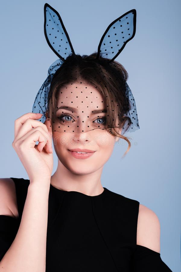Close up portrait of a fashionable brunette young woman with bunny ears royalty free stock photos
