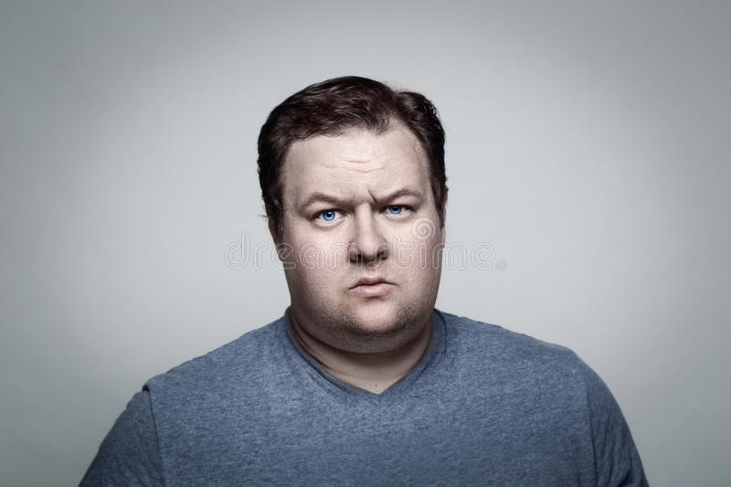 Close up portrait of fat man in studio sceptical royalty free stock images