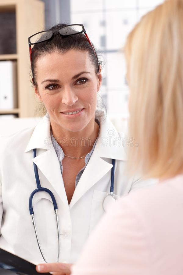 Close up portrait of female doctor with patient. Close up portrait of happy female brunette doctor with patient. Wearing glasses, stethoscope and lab coat stock image