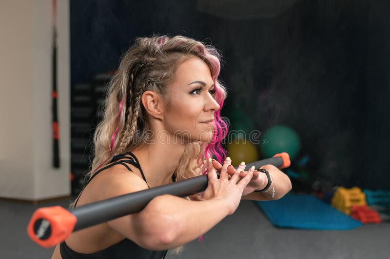 Close-up portrait of fitness woman with blond and pink long hair doing squats exercise with gymnastic stick. Blurred background of. Gym with copy space royalty free stock photo