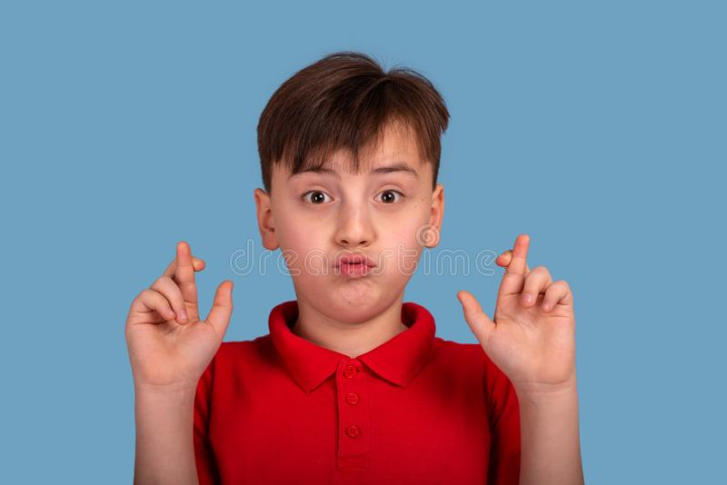 Studio portrait of a of a funny boy suggesting a desire and showing hands with crossed fingers on blue background. Close up portrait of a of a funny boy royalty free stock photography