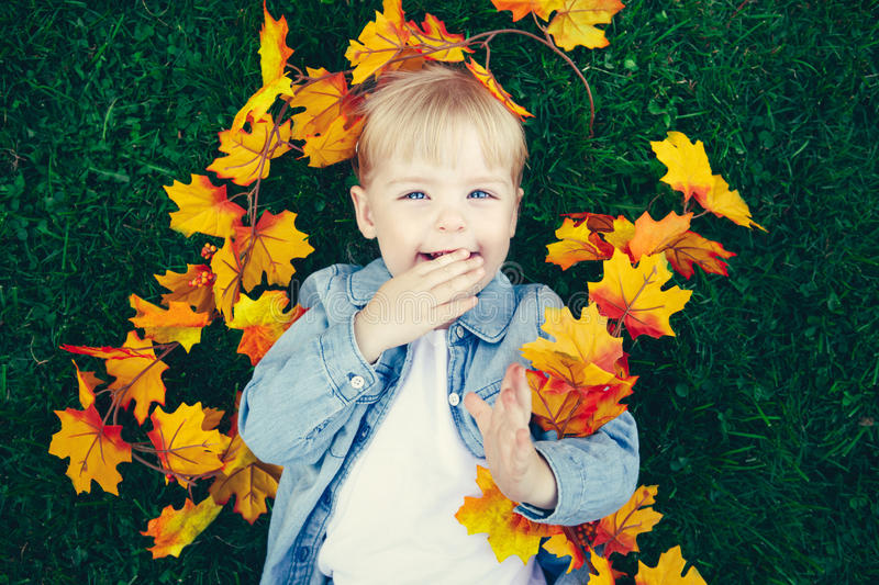 Portrait of funny cute smiling white Caucasian toddler child girl with blond hair lying on green grass with yellow autumn leaves royalty free stock photography
