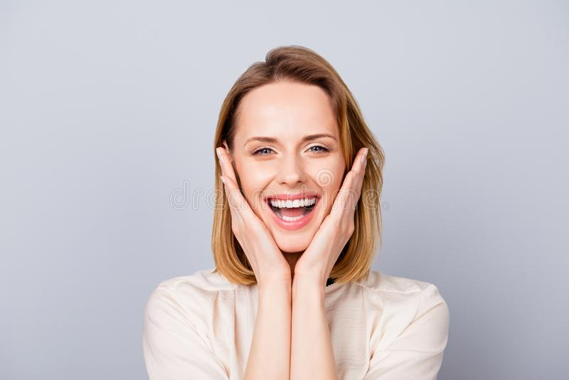 Close up portrait of funny cute young woman laughing and touching her cheeks stock image