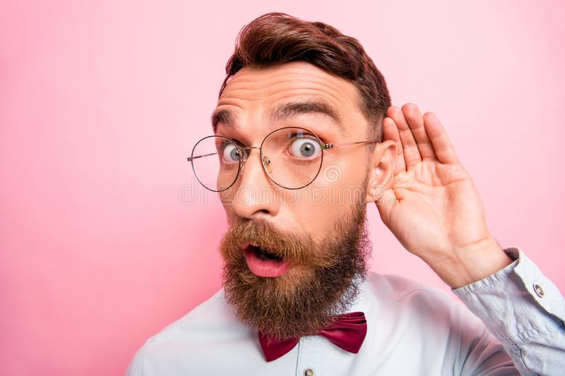 Close up portrait of funny funky loony geek astonished hipster holding palm near ear  pastel background. Close up portrait of funny funky loony geek astonished stock photo
