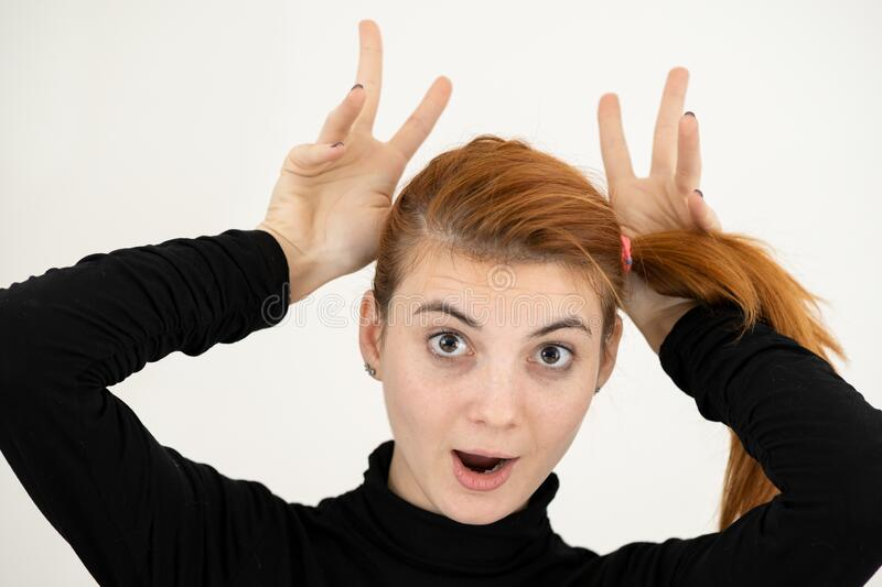 Close up portrait of funny girl holding her ears with hands like a monkey.  stock images