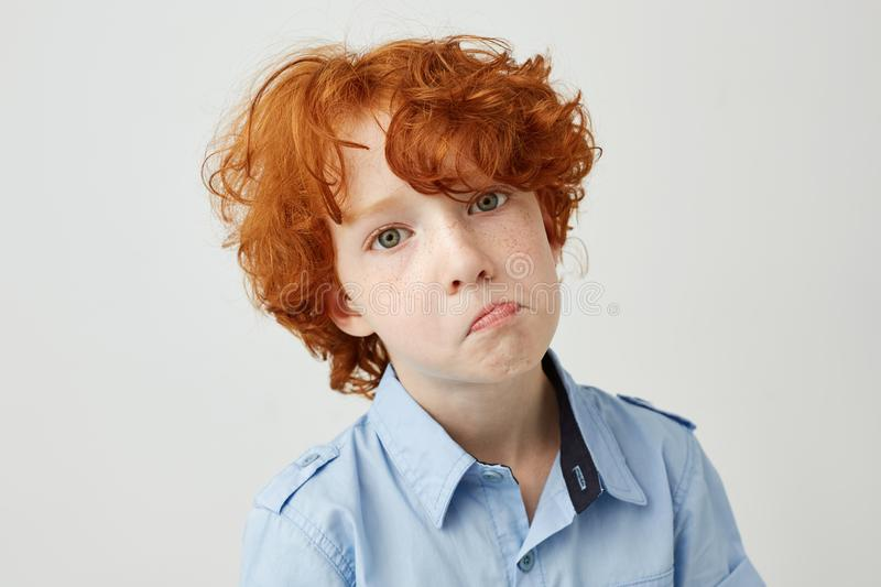 Close up portrait of funny little boy with red curly hair and freckles looking in camera with unhappy expression, after stock photography