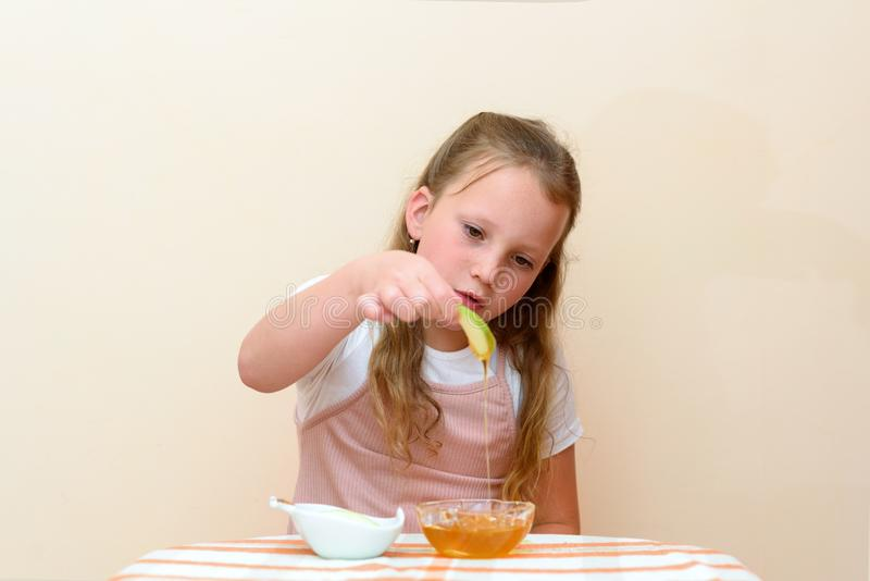 Jewish child dipping apple slices into honey on Rosh HaShanah. royalty free stock images