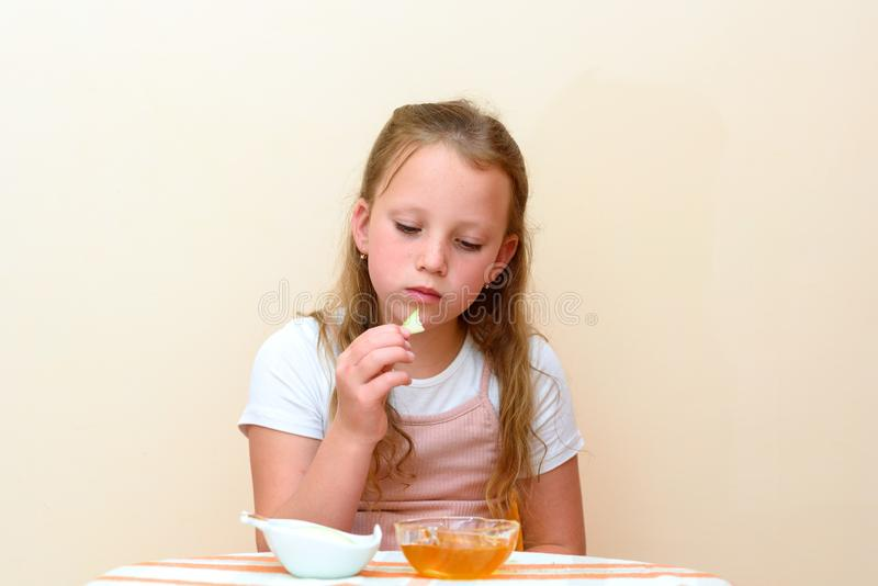 Jewish child dipping apple slices into honey on Rosh HaShanah. stock photography