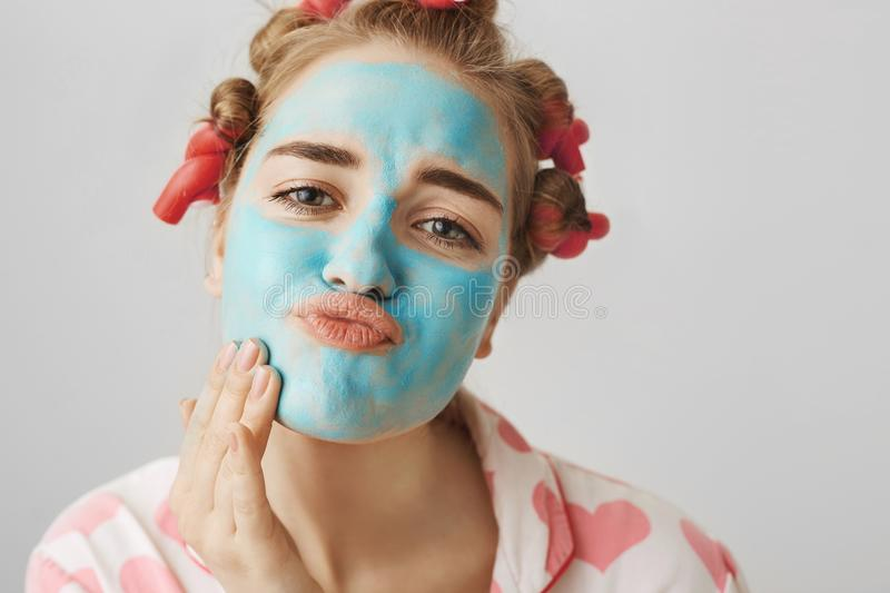 Close-up portrait of funny white woman with hair-curlers, wearing nightwear and folding lips while applying face mask. With hand, looking at camera as if in royalty free stock image