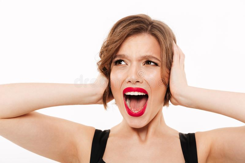 Close up portrait of a furious girl screaming. Isolated over white background royalty free stock image