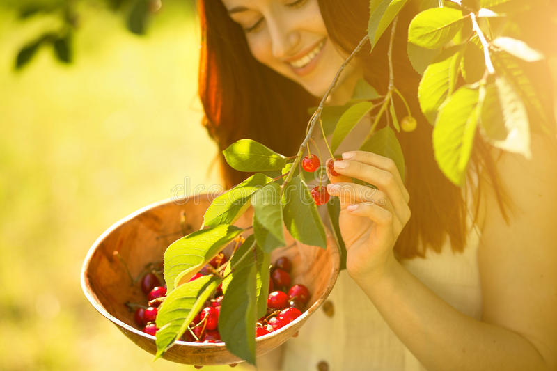 Close up portrait of ginger beautiful girl picking cherries. royalty free stock photos