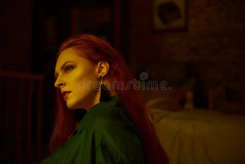 Vintage photo of Beautiful red haired young woman posing in old loft apartment in Tbilisi. Close up portrait Ginger lady posing in loft apartment in Tbilisi. She stock photo