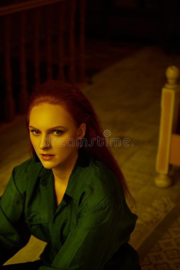 Vintage photo of Beautiful red haired young woman posing in old loft apartment in Tbilisi. Close up portrait Ginger lady posing in loft apartment in Tbilisi. She royalty free stock photography