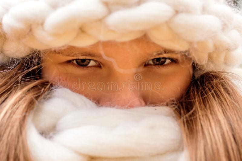 Close up portrait of the girl in a cap and scarf rough hand-knitted stock photography
