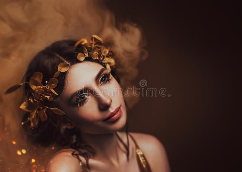 Close-up portrait. Girl with creative make-up and with golden eyelashes. The Greek goddess in a laurel wreath with. Flowers and handmade roses. Art`s Photo stock photo