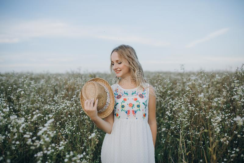 Close up portrait girl with a hat in her hand walks in a field with field flowers and smiles sincerely royalty free stock photography