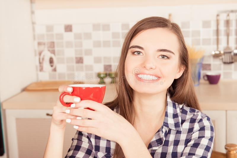 Close-up portrait of girl holding a cup of tea in the kitchen royalty free stock photos