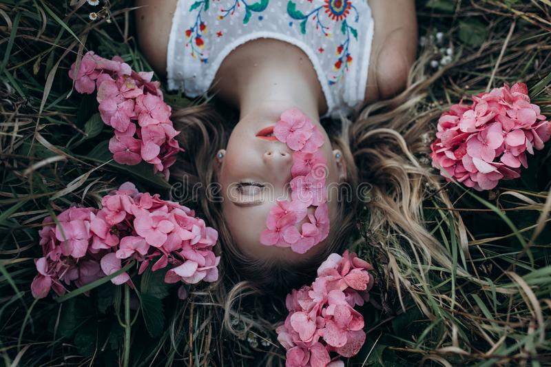 Closeup portrait of a girl lying on the ground with flowers of hydrangea in her eyes stock image