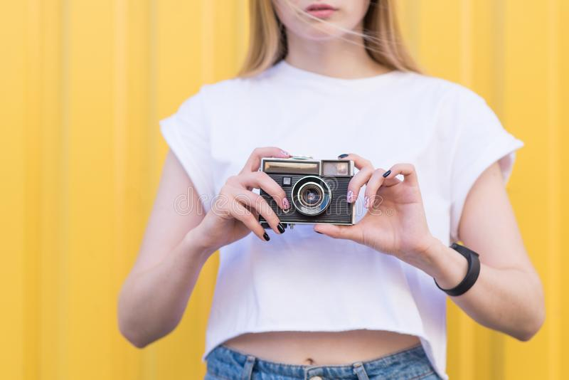 Close-up portrait of a girl with an old retro camera in her arms stock photography