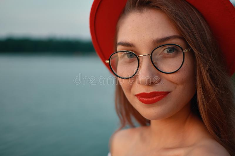 Close-up portrait girl with red lips, glasses and hat stock photo