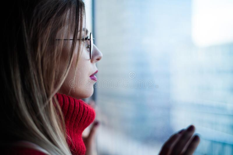 Close-up portrait of a girl in a red pullover looking out the window at the skyscrapers of the city royalty free stock photo
