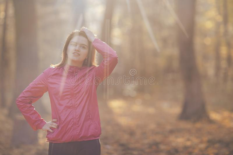 Close-up portrait of a girl who trains in the morning autumn park royalty free stock photos