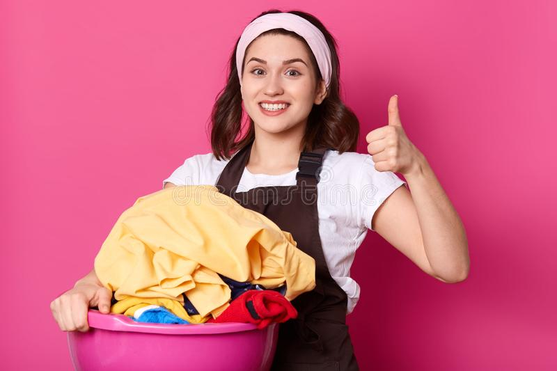 Close up portrait of good looking slender housewife holding pink basin with clean clothes, having positive facial expression, royalty free stock photography