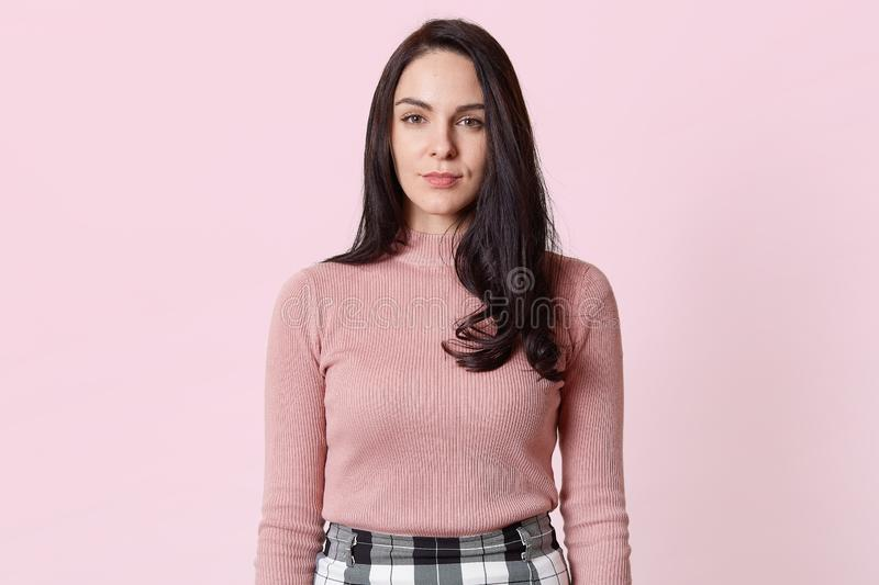 Close up portrait of good looking slender serious model standing straight over light pink background in studio, wearing jumper and stock photos