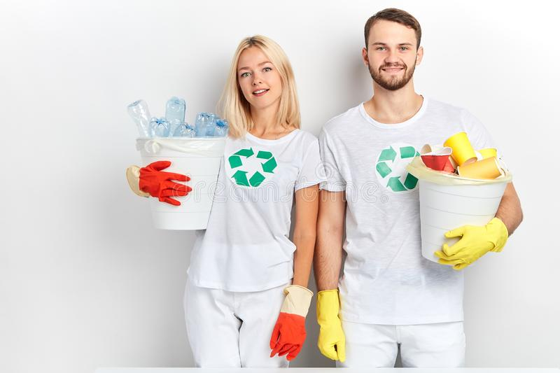 Close up portrait of good looking tired volunteers holding garbage bags  on white background royalty free stock photography