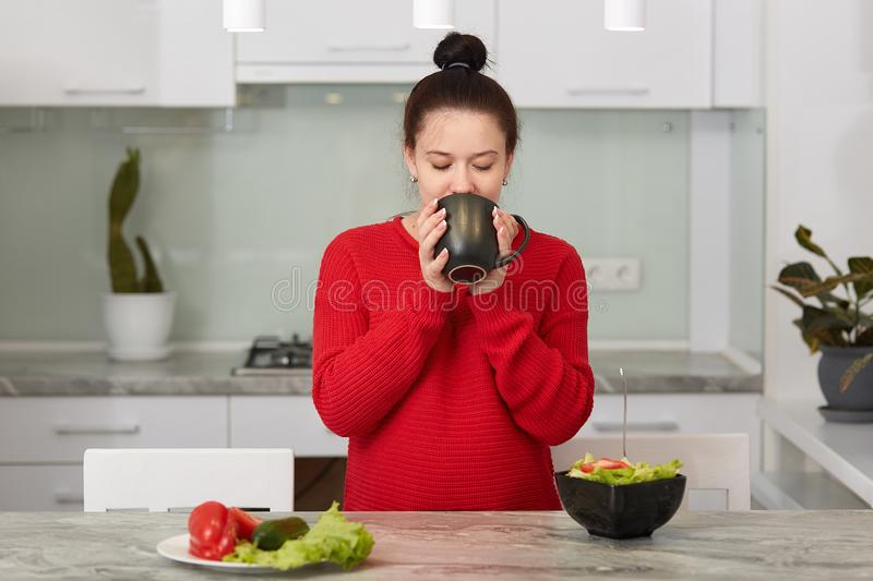 Close up portrait of good looking woman keeps cup of tea or coffee with both hands, drinks hot beverage, pregnant female poses stock image