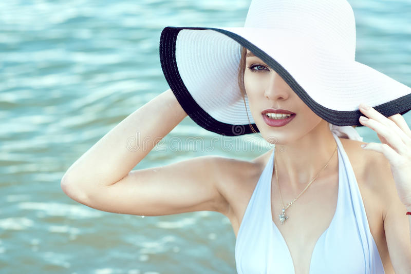 Close up portrait of gorgeous elegant glam lady hiding the half of her face behind the wide brim hat stock images