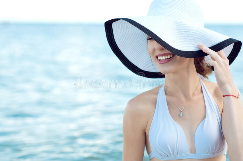Close up portrait of gorgeous glam smiling lady hiding the half of her face behind the wide brim hat stock photo