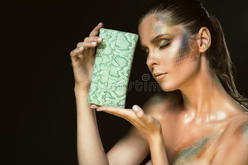 Close up portrait of gorgeous woman with closed eyes and artistic snakeskin make up holding green leather purse at her face stock image