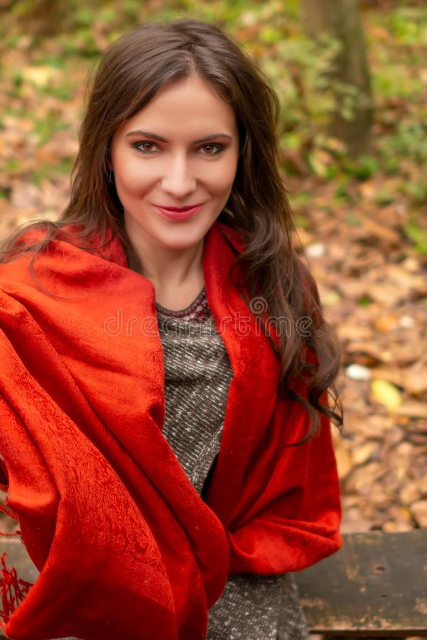 Close-up portrait of a gorgeous young woman outdoors, in a park autumn scenery, looking at the camera and smiling happy royalty free stock photos