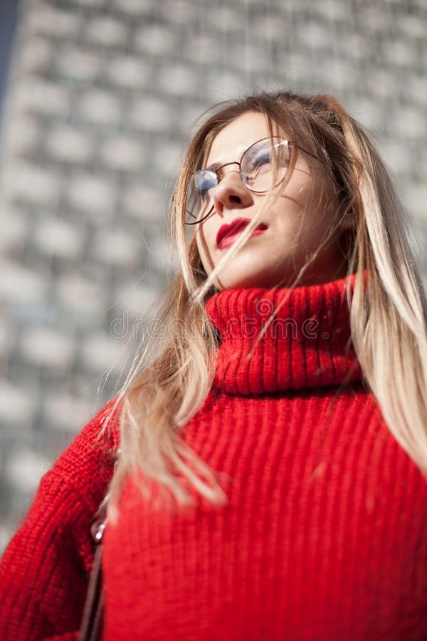 Close-up portrait of a gorgeous young woman wearing glasses and a red woolen sweater on a tall skyscraper background. Beauty, royalty free stock photos