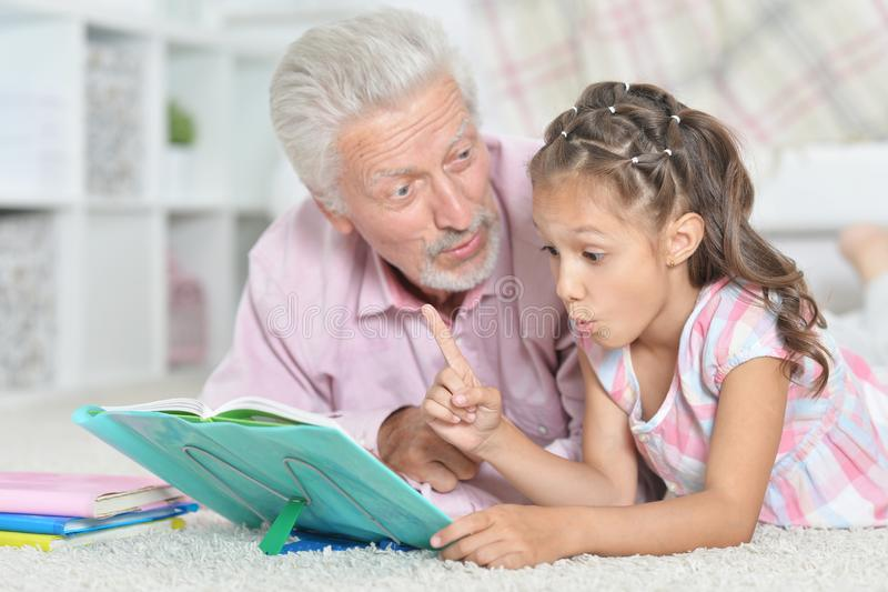 Close-up portrait of grandfather reading book with his little granddaughter. Grandfather reading book with his little granddaughter at home stock image