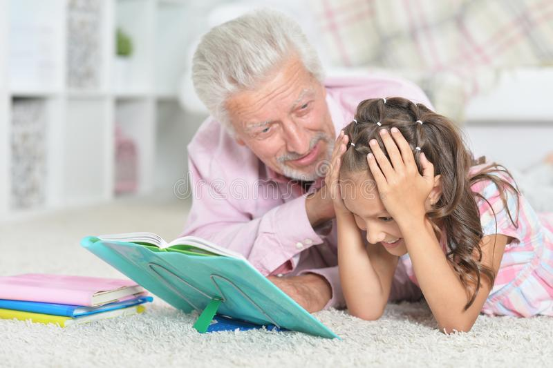 Close-up portrait of grandfather reading book with his little granddaughter. Grandfather reading book with his little granddaughter at home stock photography