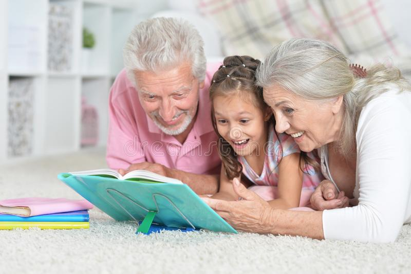 Close-up portrait of grandparents reading book with little granddaughter. Beautiful grandparents reading book with little granddaughter at home royalty free stock photos