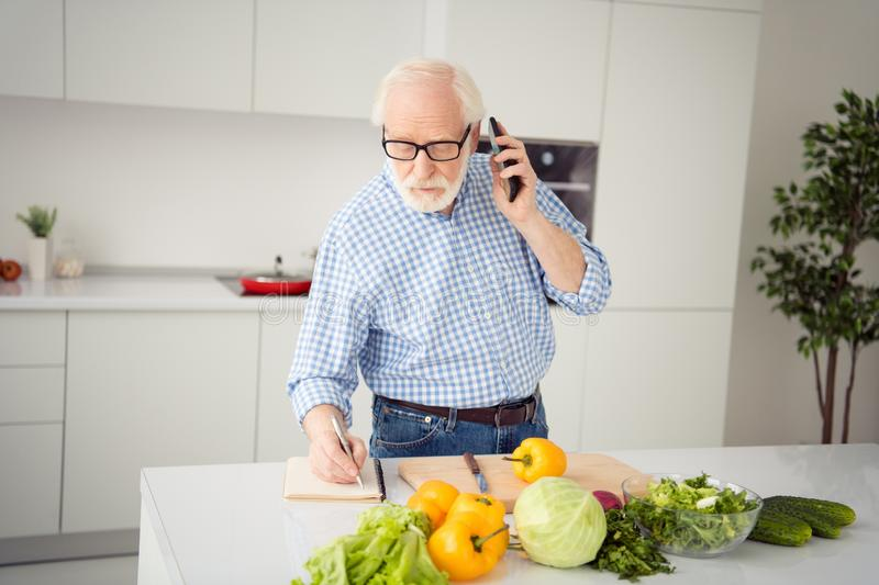 Close up portrait grey haired he his him grandpa hand arm telephone smart phone write down pen family recipe waiting royalty free stock photography