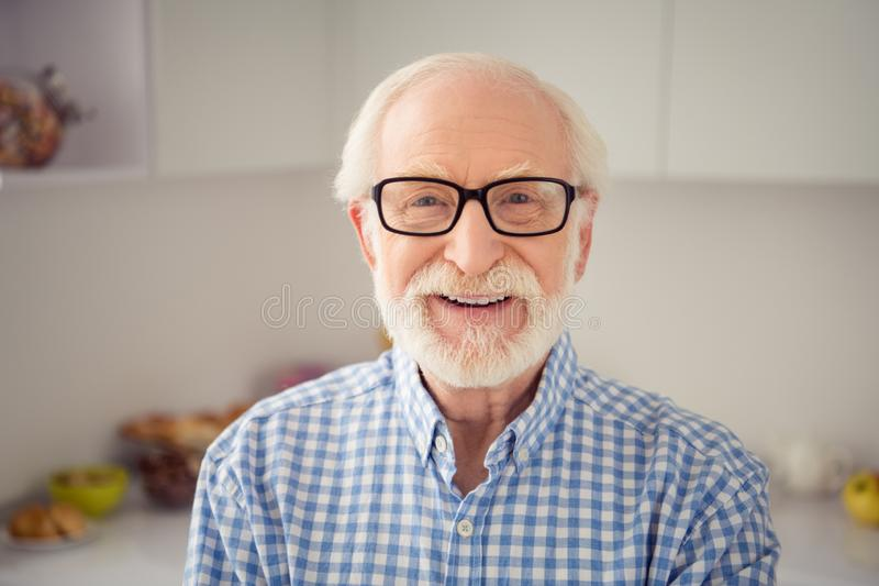 Close up portrait grey haired he his him grandpa sincerely gladly toothy smiling wearing specs casual checkered plaid stock photography