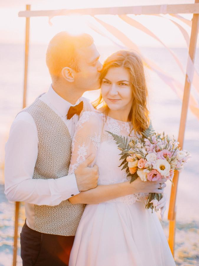 The close-up portrait of the groom kissing the bride on th head at the background of the sunset. royalty free stock photography