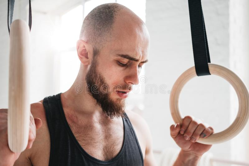 Close up portrait of gymnast male taking rest after intense dip ring workout at gym stock image