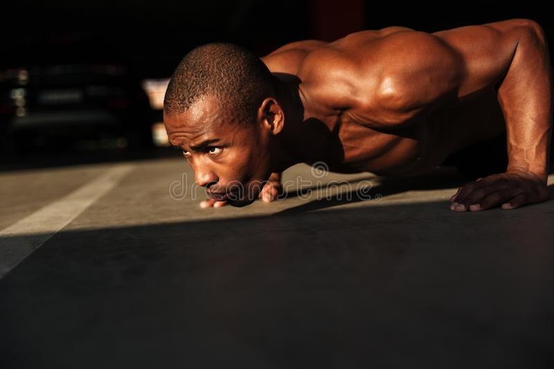 Close up portrait of a half naked afro american sportsman. Close up portrait of a half naked serious afro american sportsman doing push ups indoors royalty free stock photography