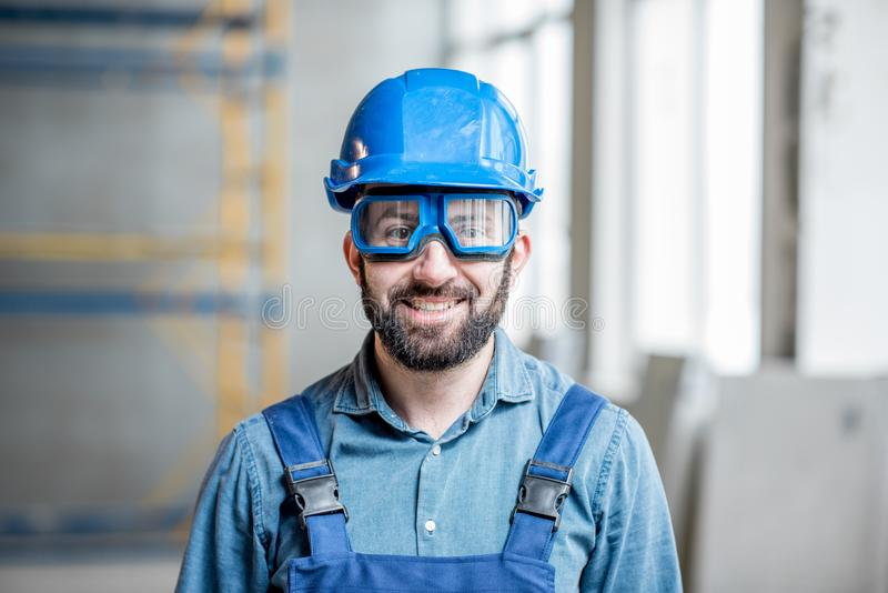 Builder in uniform indoors. Close-up portrait of a handsome bearded builder with protective glasses and helmet indoors stock photos